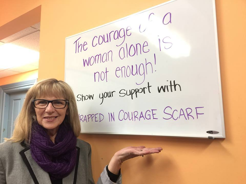 "image of woman wearing a purple scarf, gesturing to a sign reading ""The courage of a woman alone is not enough! Show your support with a Wrapped in Courage scarf."""