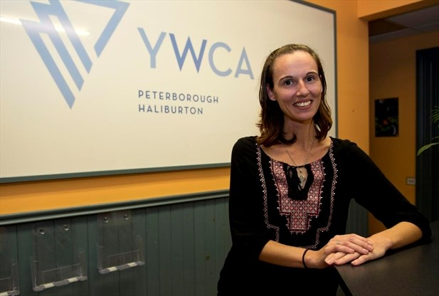 Image of Carissa McIntyre, smiling in front of the YWCA logo