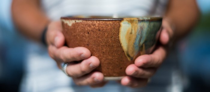 Image of a woman's hands holding out a handmade bowl