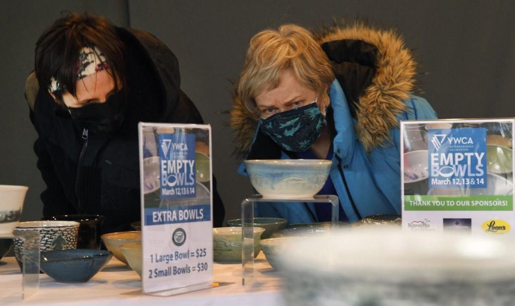 Image of two women wearing COVID masks looking closely at ceramic bowls at the YWCA Empty Bowls event