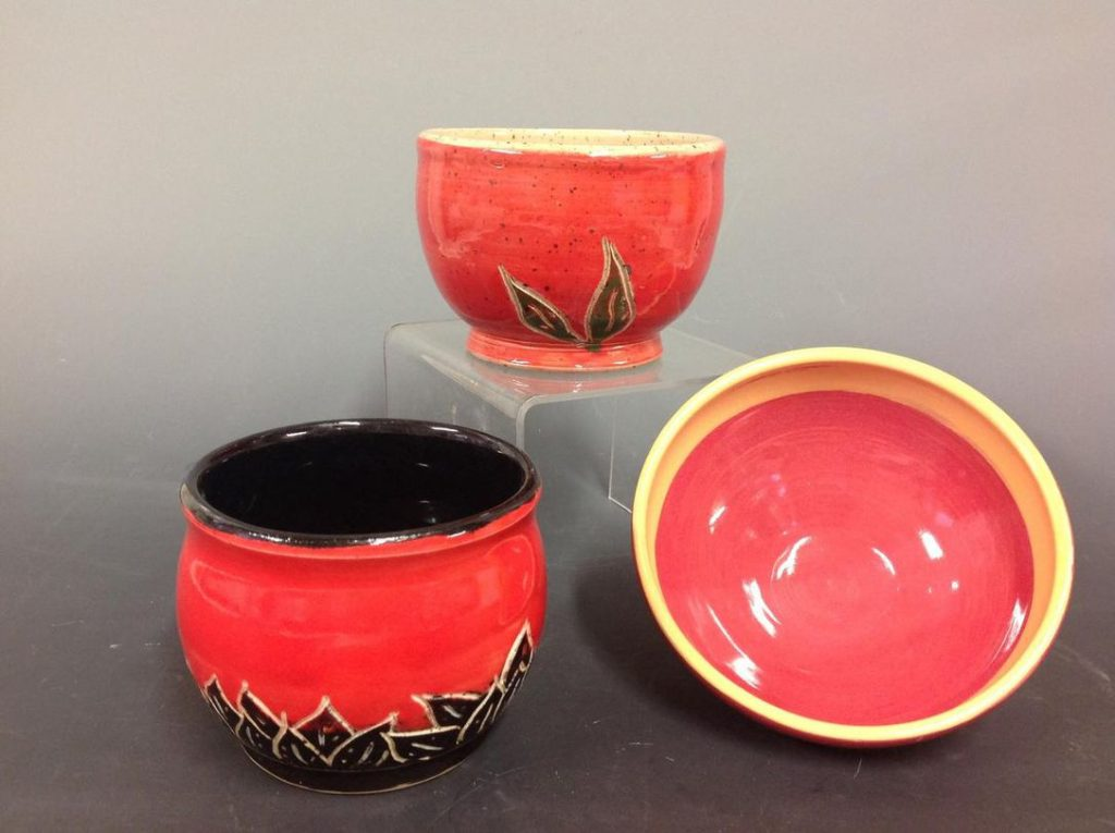 Image of three red and black ceramic bowls arranged in a display