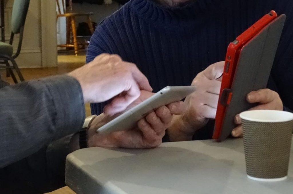 Image of two pairs of seniors' hands holding an iphone and tablet