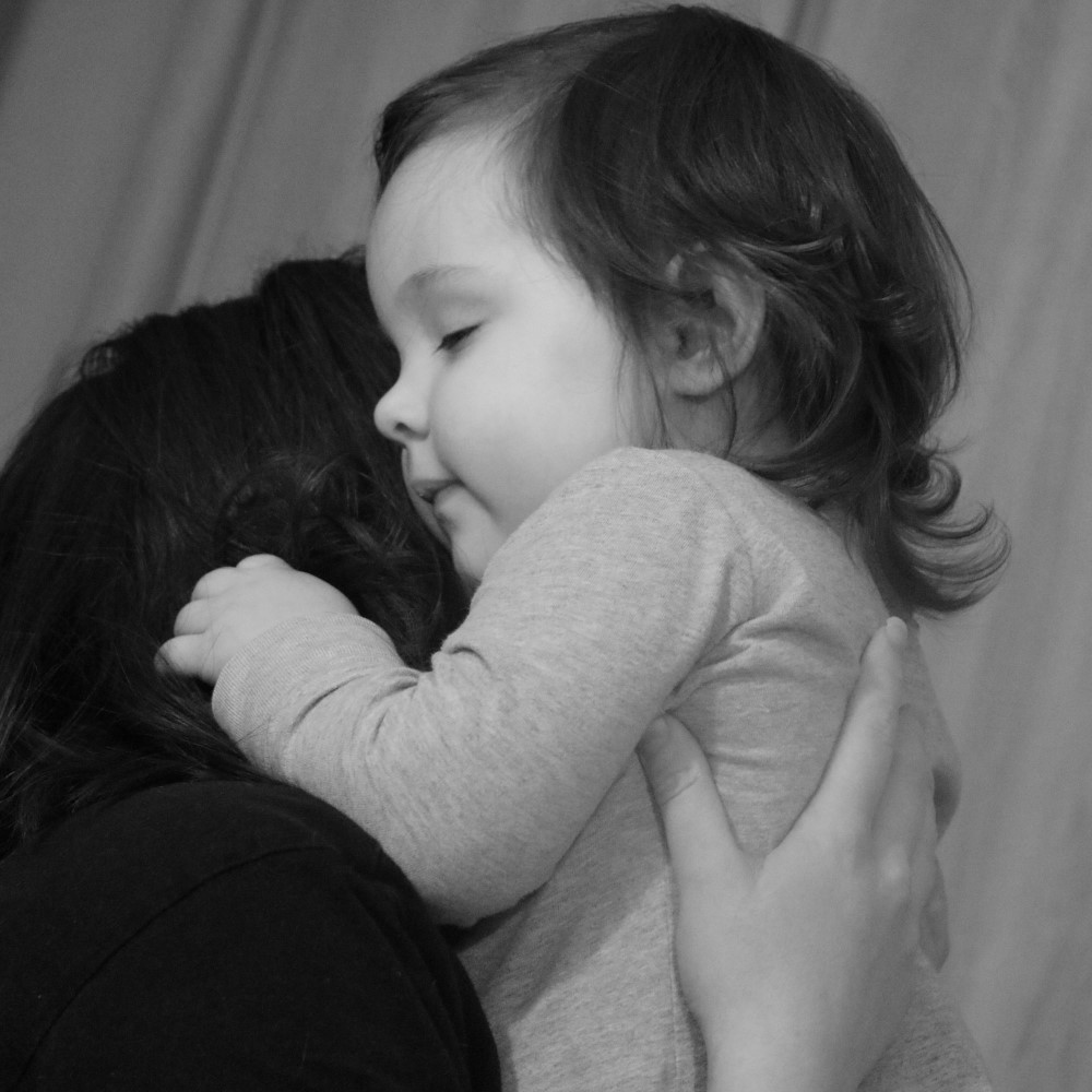 black and white image of a small child being held in her mother's arms